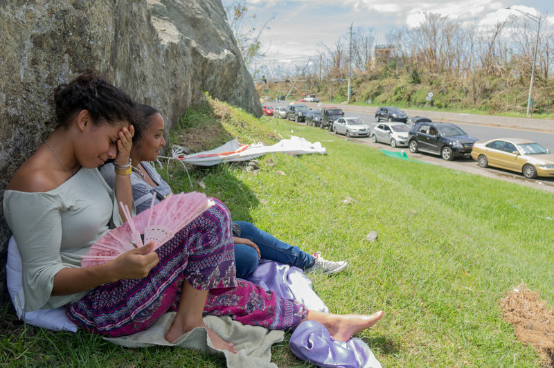 Kiara Rodriguez de Jesus, 23, (left) and friend Stephanie Norat, 26, find shade as people wait in line at the Gulf Route 65 gas station for a gasoline tanker scheduled to arrive.