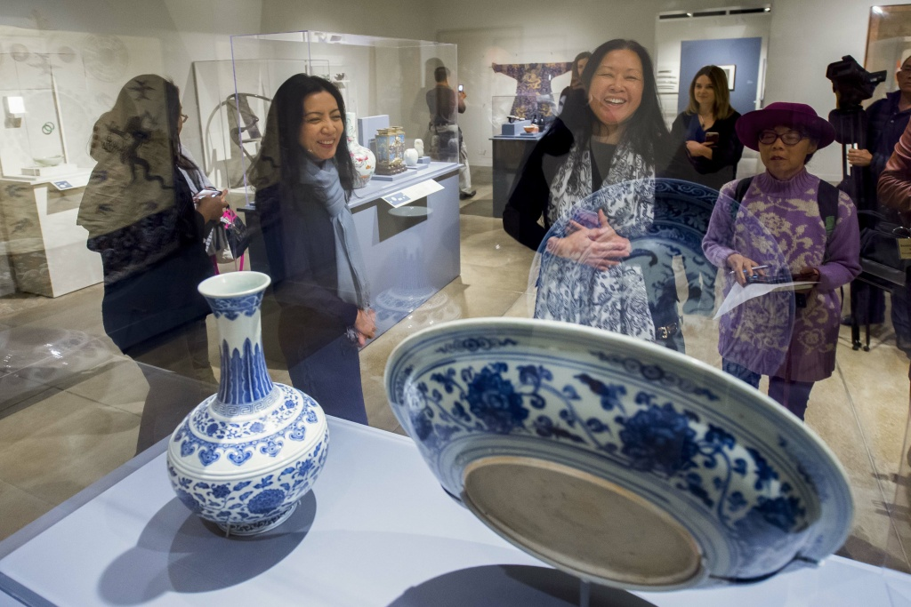 Christina Yu Yu (left), director of the USC Pacific Asia Museum, points out a cobalt-oxide porcelain charger and vase from the early Ming dynasty.