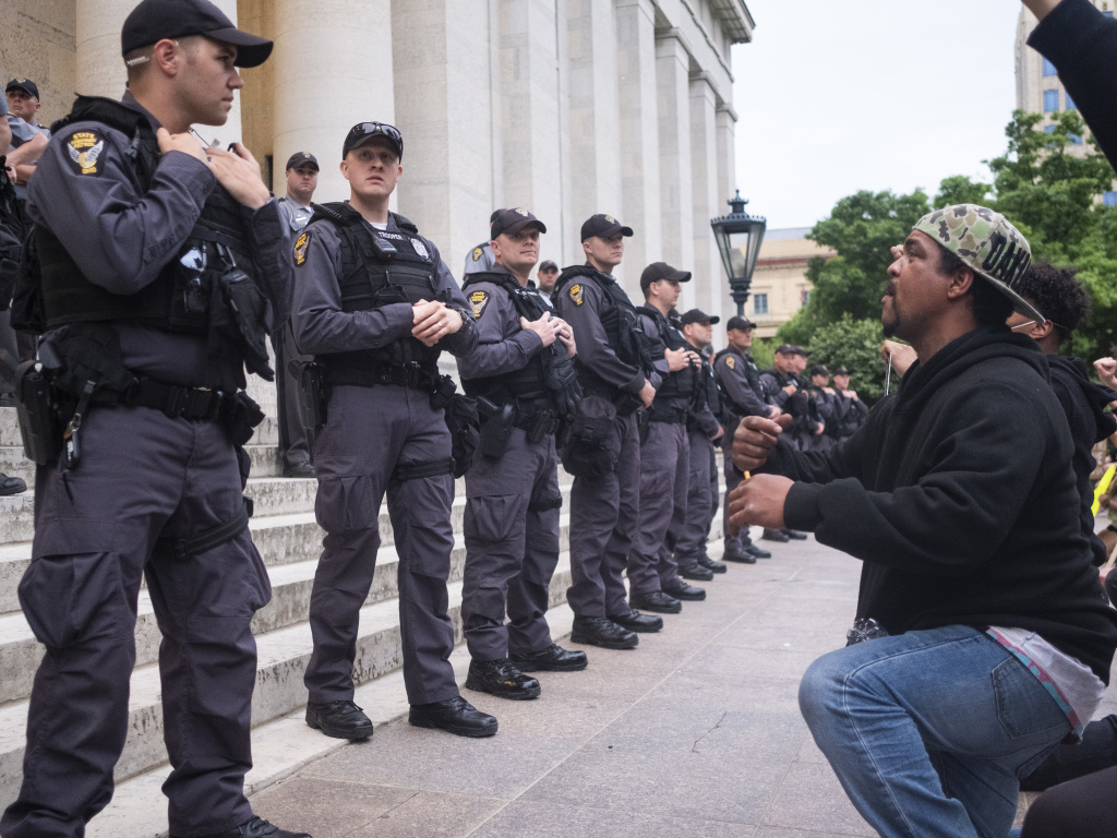 Protesters chant for Ohio state troopers and Columbus police to take a knee with them in solidarity on the Ohio Statehouse steps on June 1, 2020, in Columbus. A federal judge has ordered Columbus police to stop using force against nonviolent protesters.