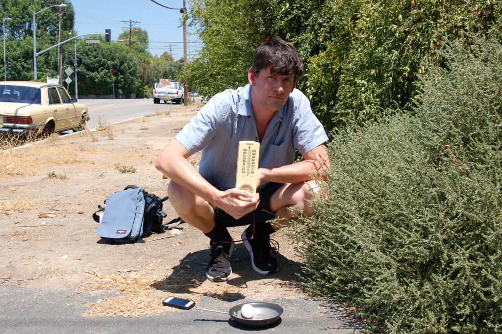 KPCC's John Rabe in Sherwood Forest preparing to fry an egg on the sidewalk.
