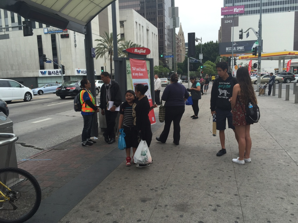 Passengers line up at the 720 Rapid stop at Wilshire and Vermont, one of two stops where Metro is piloting all-door boarding.