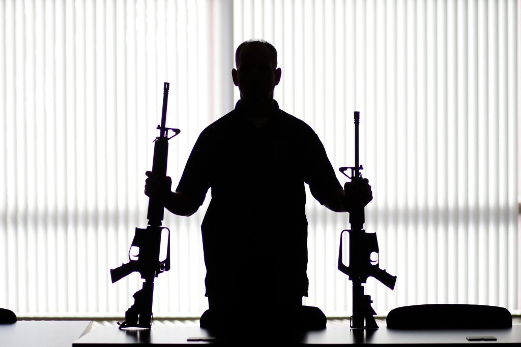 An ATF agent poses with homemade rifles, or