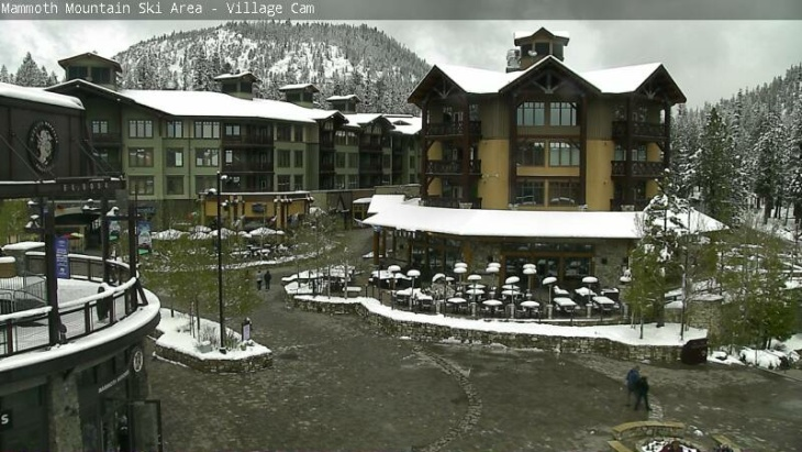 Mammoth Mountain's Village Cam shows snow gathering on trees and rooftops after an unseasonably cold spring storm dropped more than a foot of snow on the resort.
