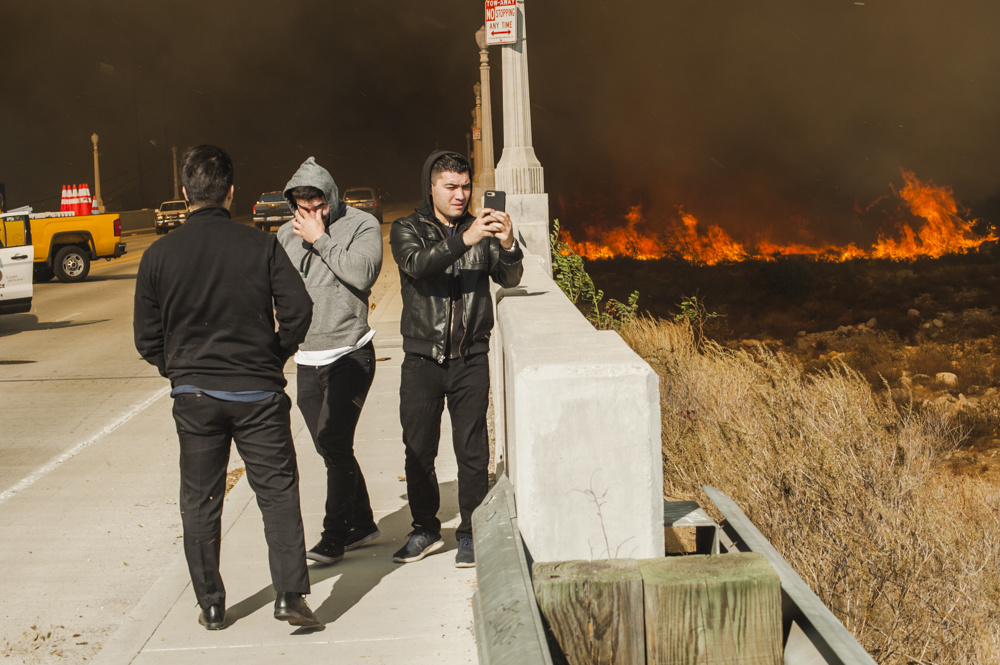 People take photos on their cell phones at the edge of the Creek Fire in Lakeview Terrace on Dec. 5, 2017.