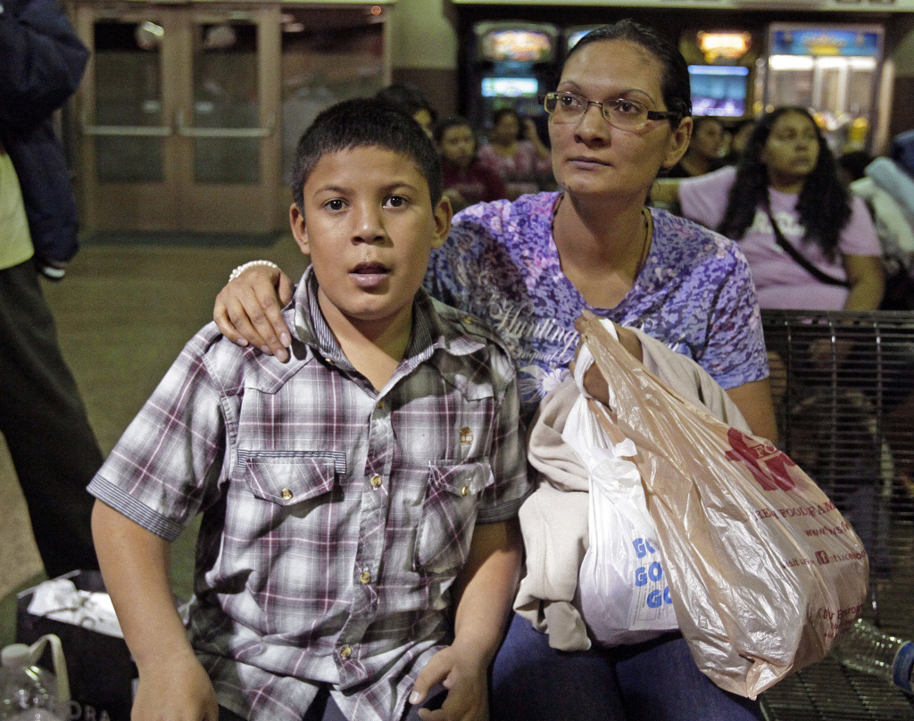 A mother and son in Arizona who've entered the US illegally, sitting at the bus station. Immigration officials say they are dealing with an influx of migrants coming from Central America, many of them unaccompanied minors.