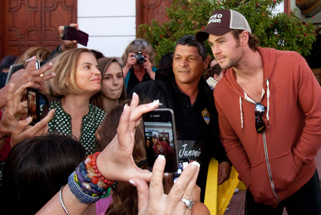 Australian actor Chris Hemsworth (R) poses with fans in Playa de Santiago, on the Spanish Canary island of La Gomera on November 23, 2013, during the shooting of the film 'In the Heart of the Sea' by US director Ron Howard. With its outrigger canoes and sailing whaler anchored off the coast, a Hollywood blockbuster started shooting more than three months ago in the small port of Playa de Santiago, where the few bars and restaurants are now always full thanks to the production. A godsend, welcomed in this region of Spain battered by the crisis and an unemployment rate reaching 35.1%.