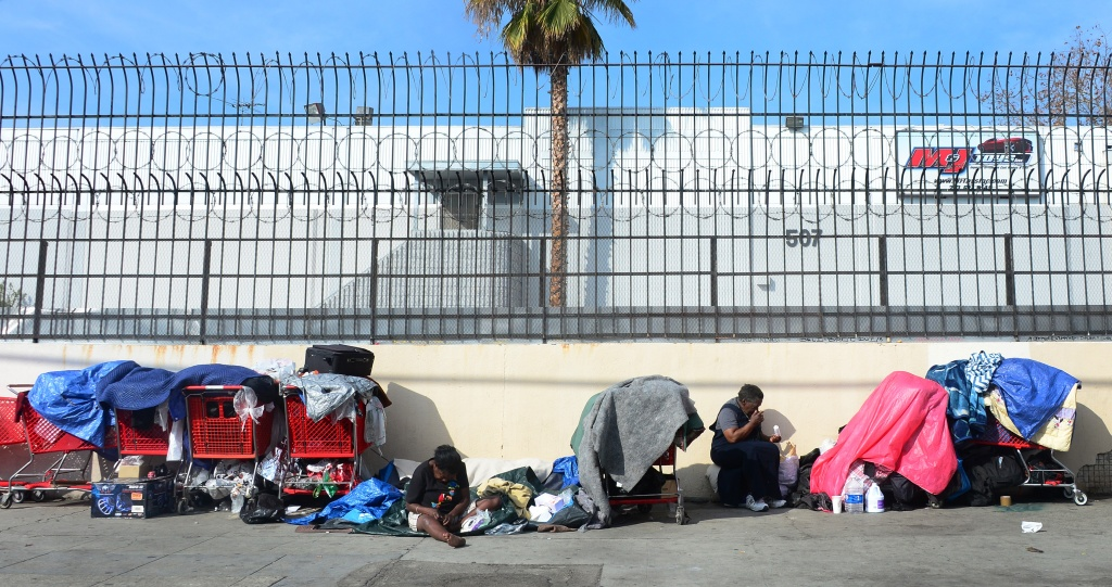 Homeless women sit amid their belongings on a street in downtown Los Angeles, California.