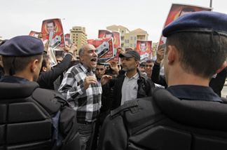 Lebanese riot policemen stand guard as Syrian protesters carry pictures of Syrian President Bashar Assad as they shout pro-government slogans in front of the U.N. house in downtown Beirut, Lebanon, Monday, May 2, 2011.