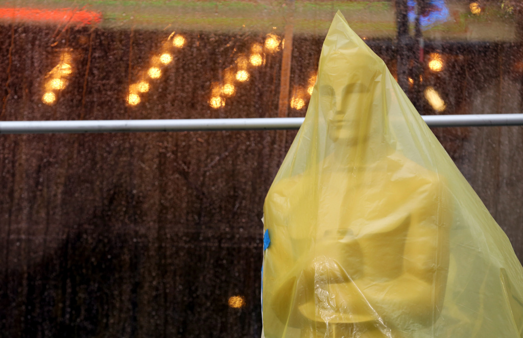 An Oscar statue covered in plastic stands on the red carpet as preparations are made during rainy weather for the 86th Academy Awards in Los Angeles.