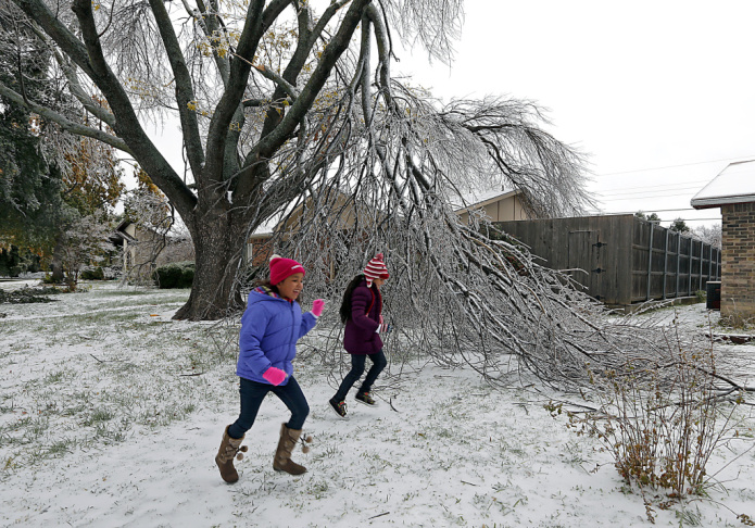 Enari Hernandez, left, 6, and her cousin Maritza Jimenez, 6, play in front of a damaged tree in their neighbors yard on Saturday in Plano, Texas.