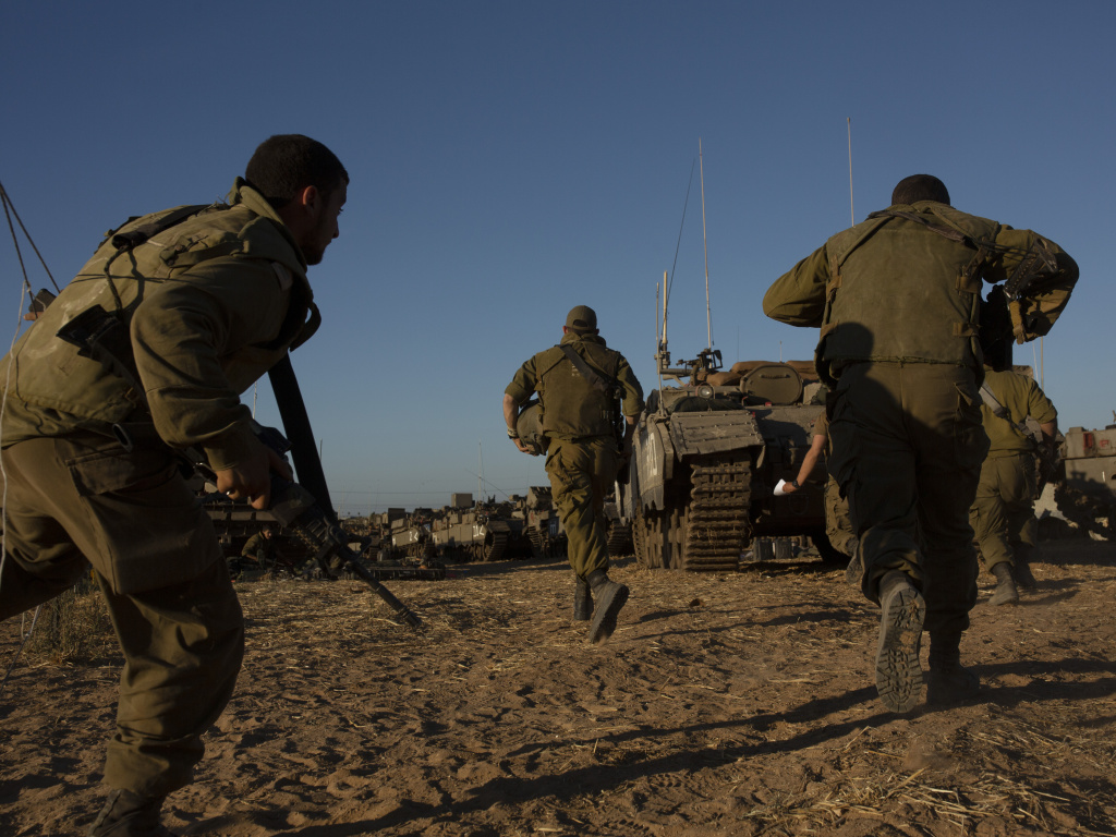 Israeli soldiers run for cover under armored vehicles as a siren sounds warning of incoming rockets fired from Gaza strip in a staging area near the Israeli-Gaza border southern Israel, Saturday, May 15, 2021.