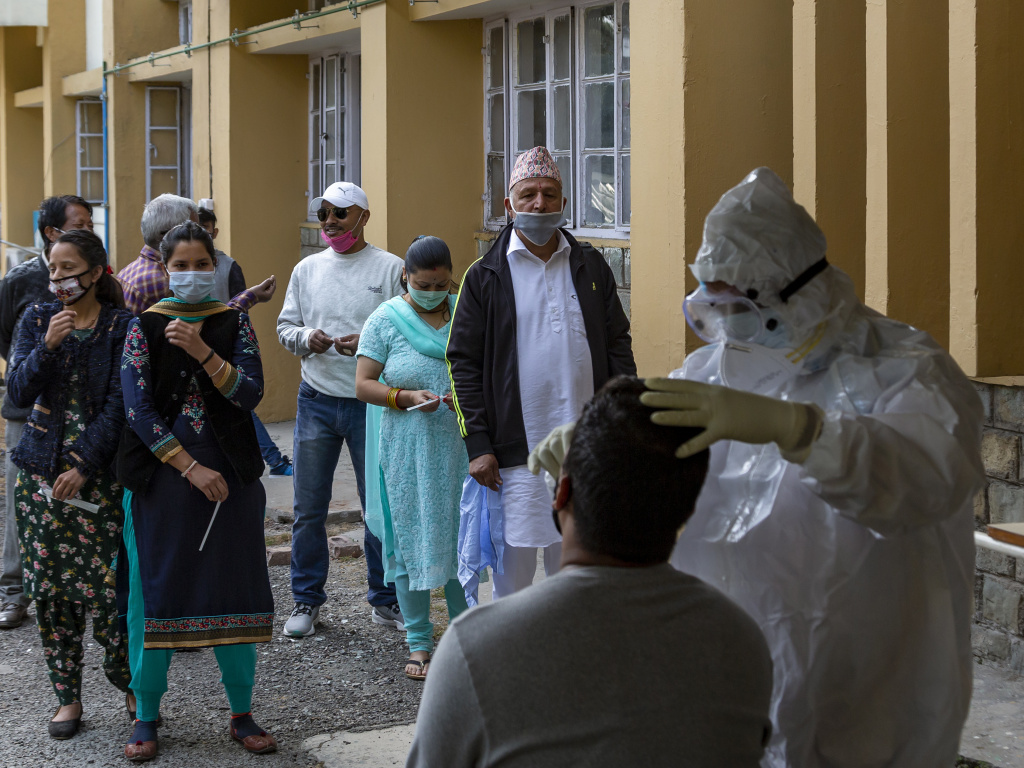 A health officer in protective suit collects a swab sample to be tested for coronavirus on Thursday in Dharmsala, India. India's confirmed  coronavirus caseload surpassed 8 million on Thursday.