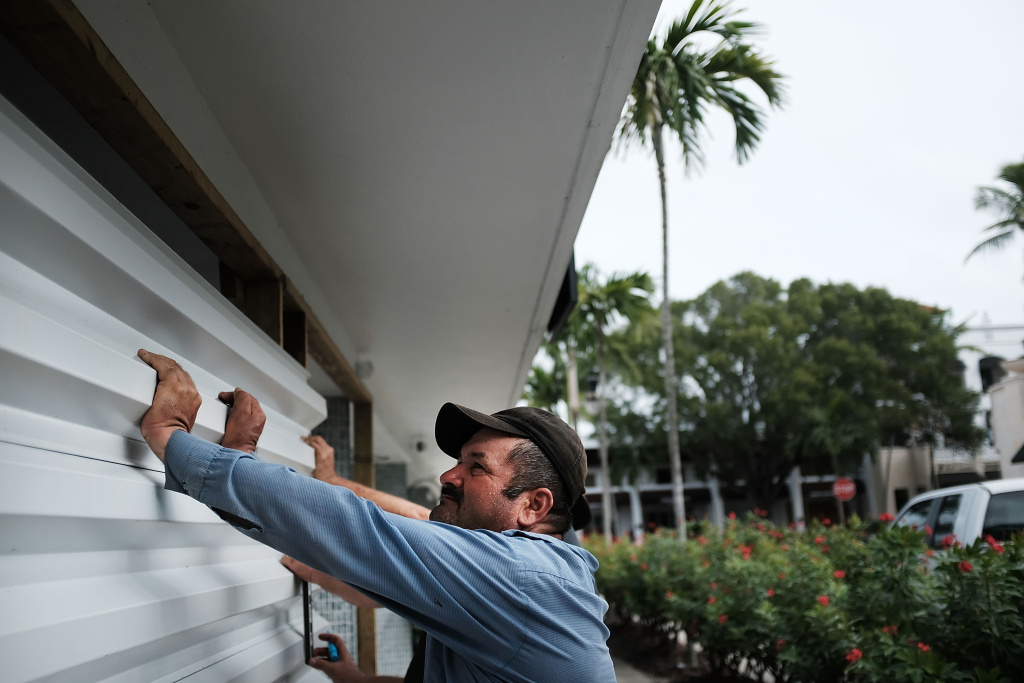 Men put up metal siding at a business in Naples, Florida before the arrival of Hurricane Irma on September 9, 2017.