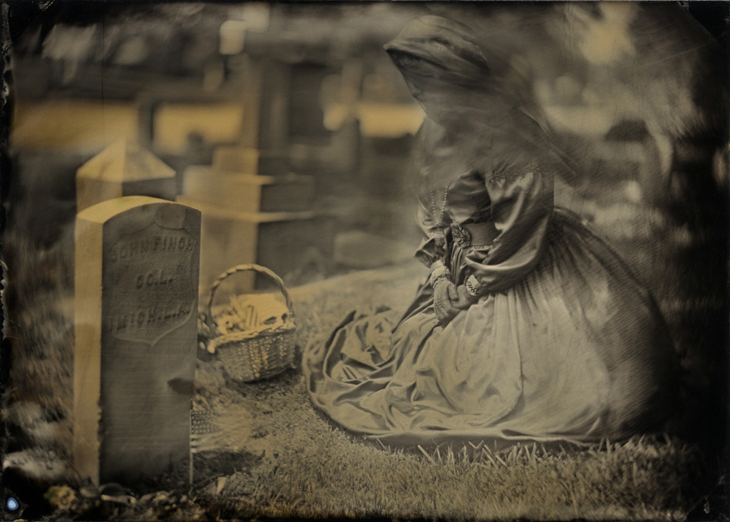 Wearing a mourning outfit complete with veil, a woman pays tribute to fallen soldiers at a Veteran's Day memorial in San Gabriel, California. Wet plate photograph.