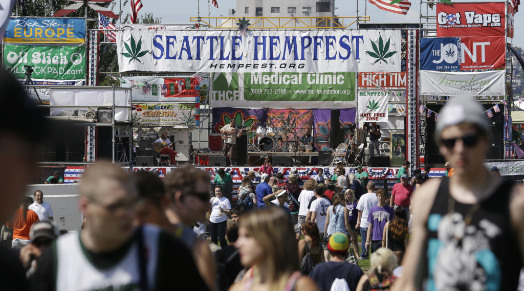 People walk past the main stage at the first day of Hempfest, Friday, Aug. 16, 2013, in Seattle. Thousands packed the Seattle waterfront park for the opening of a three-day marijuana festival — an event that is part party, part protest and part victory celebration after the legalization of pot in Washington and Colorado last fall. Hempfest was expected to draw as many as 85,000 people per day.