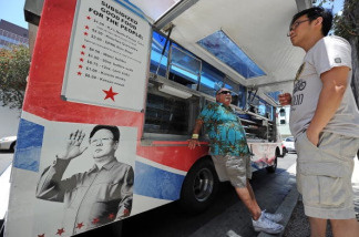 A customer reads the menu on the 'Pyongyang Express' food truck in Los Angeles.