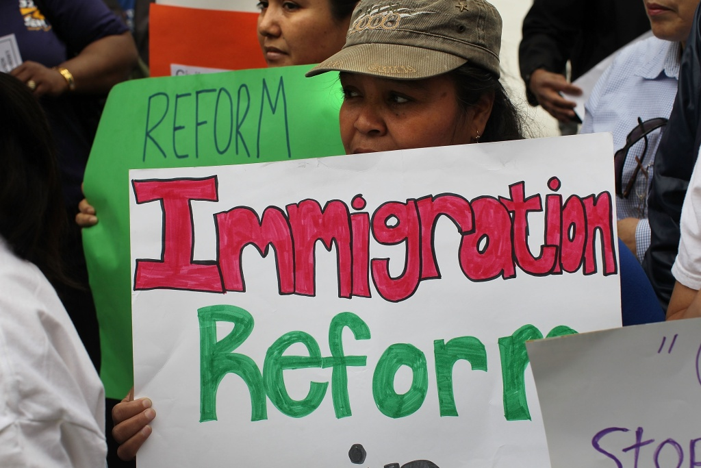 A protestor's sign at an immigration rally. Now that a deal on guest workers has been struck between business and labor, some members of a bipartisan Senate group working on an immigration reform plan say that a draft bill could be ready within the coming week.