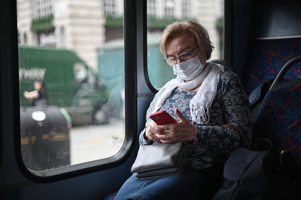 A passenger wearing a protective face covering to combat the spread of the coronavirus, checks her phone while travelling on a bus along Oxford Street in central London on July 5, 2021.
