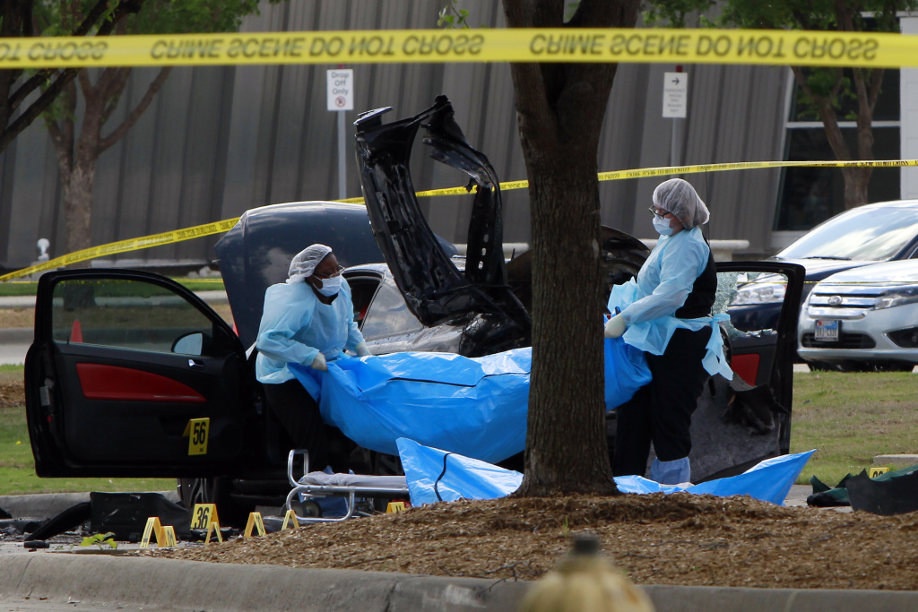 Investigators remove a body as they work a crime scene outside the Curtis Culwell Center after a shooting occurred the day before May 04, 2015 in Garland, Texas. During the