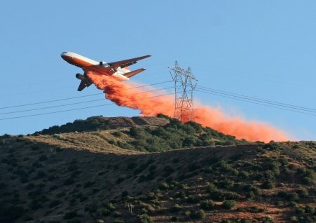 A large firefighting plane drops fire retardant on a mountain ridge near power lines. The retardant landing on  insulators can cause a high power line to short out.