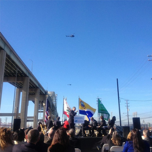 Helicopters are hovering at the height of the new replacement bridge to the Gerald Desmond Bridge, which links the Ports of Los Angeles and Long Beach to the 710 freeway. The flight took place at an event marking the start of construction of the new span on January 8, 2013.