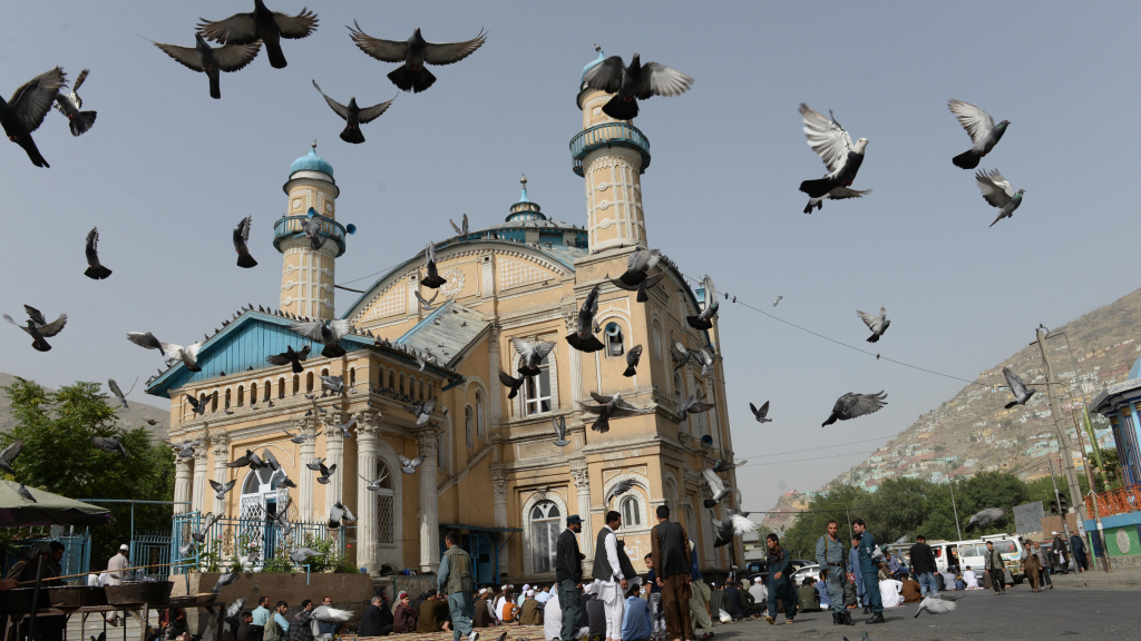 Pigeons fly into the air as Muslims offer prayers at the start of the Eid al-Fitr holiday, which marks the end of Ramadan, at the Shah-e Do Shamshira Mosque in Kabul on Friday. This Eid, Afghans welcomed the start of the Taliban's first ceasefire since the 2001 U.S. invasion