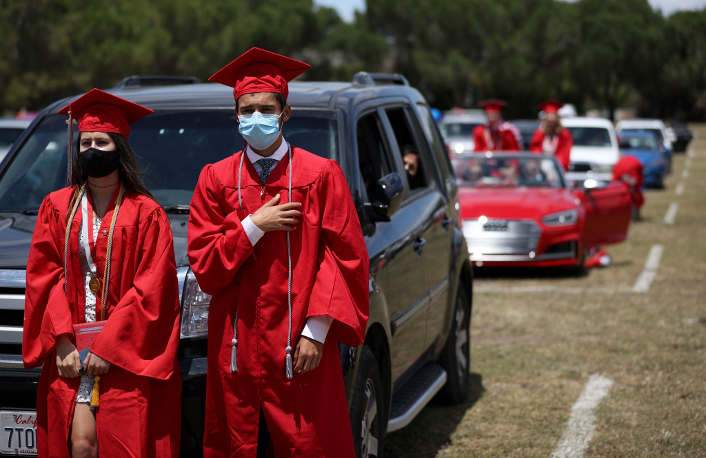 Redwood High School seniors recite the pledge of allegiance during a drive-in graduation ceremony at the Marin County Fairgrounds on June 12, 2020 in San Francisco, California.