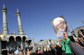 Iranians hold portraits of Iranian cleric Grand Ayatollah Hossein Ali Montazeri during his funeral procession in the holy city of Qom on December 21, 2009.