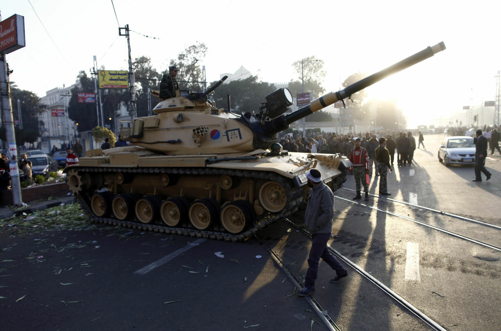 Egyptians walk past army tanks deployed near the presidential palace in Cairo after five demonstrators died overnight in clashes between supporters and opponents of Islamist President Mohamed Morsi on December 6, 2012. Morsi was expected to issue a statement to address the worst violence since his June election, which has pitted Islamists against an opposition that has escalated protests since he assumed extensive powers on November 22.