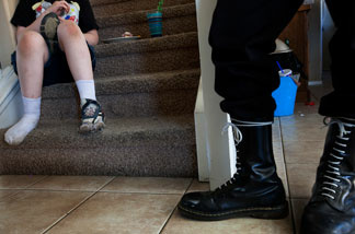 Jeff Hall's son sits on the stairs holding his shoe and eating a sandwich while a National Socialist Movement member stands near him in Hall's Riverside home.
