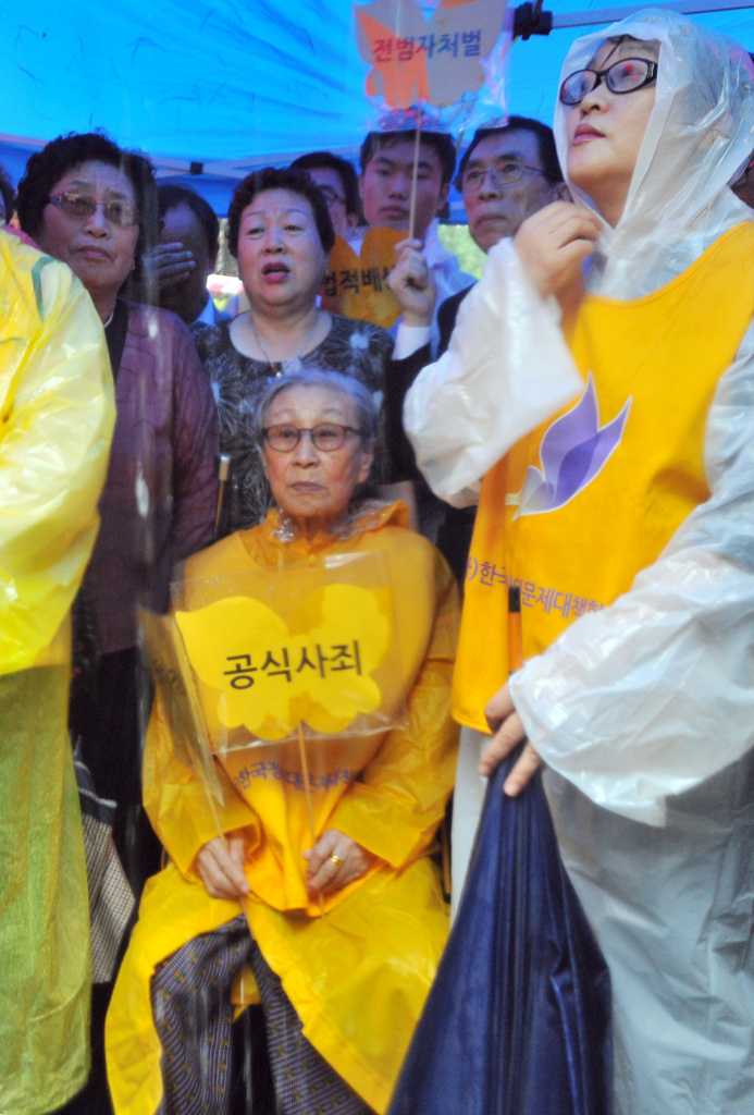 "The issue of Japan's use of Korean, Chinese and Southeast Asian women and girls as sex slaves - euphemistically called ""comfort women"" - continues to alienate Tokyo from its neighbors nearly 70 years after the war's end. (Photo: A South Korean former 'comfort woman' (center), who was forced to serve as a sex slave for Japanese troops during World War II, holds a butterfly-shaped placard reading 'official apology,' during the 1,035th weekly protest against Japan in front of the Japanese embassy in Seoul on August 15, 2012."