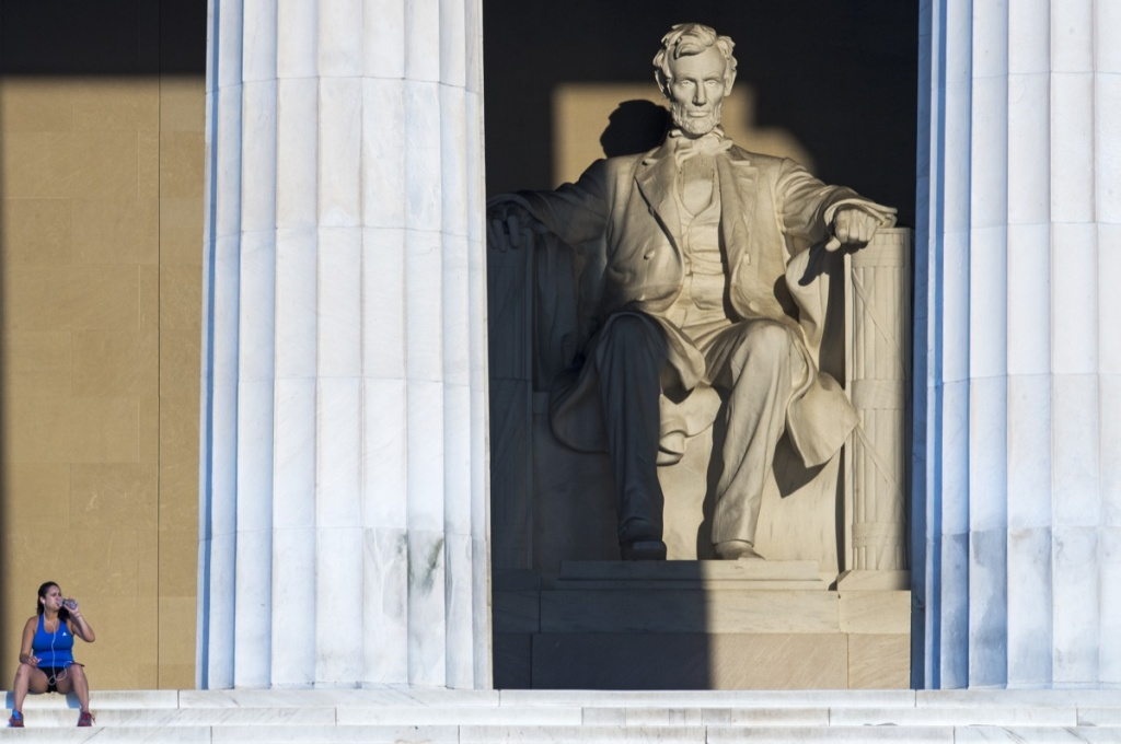 A jogger takes a break as the early morning sun shines into the Lincoln Memorial Aug. 13, 2012, in Washington, D.C.