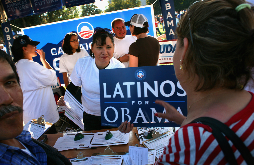 Democratic Party workers hand out signs at a celebration marking Mexican Independence Day in Denver, Colorado.
