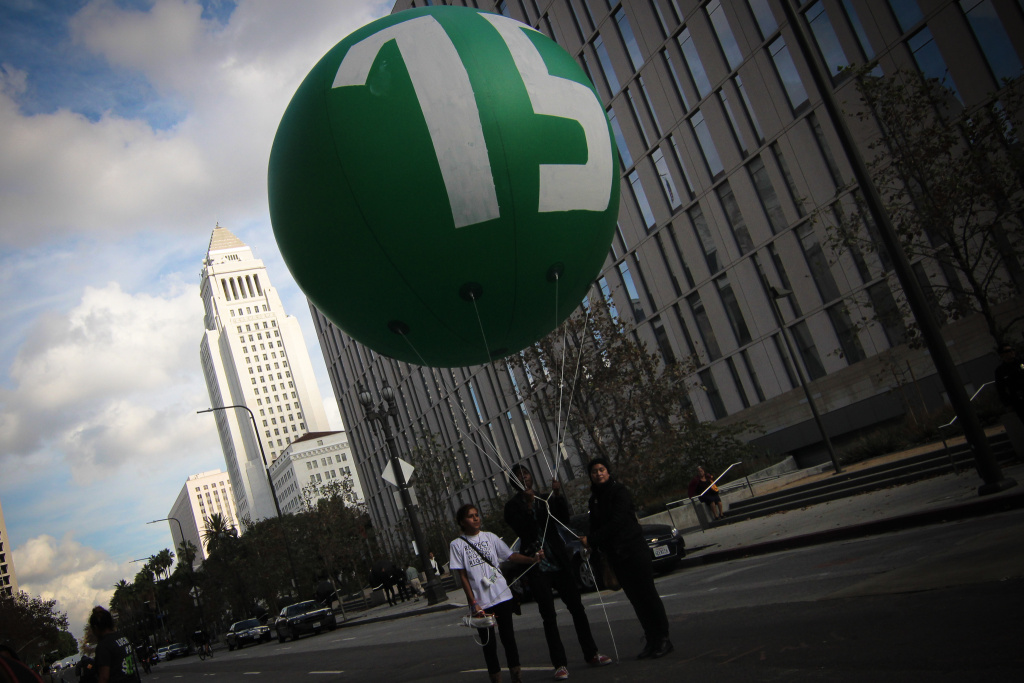 The Los Angeles City Council on Tuesday, May 19, 2015, approved a proposal that calls for raising the city's minimum wage to $15 an hour by 2020. (File photo shows balloon used during a rally and march to demand the increase to $15.)