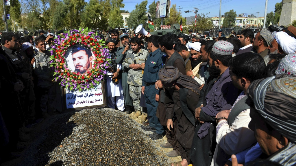 Mourners stand beside the grave of Gen. Abdul Raziq, the Kandahar police chief who was killed by a Taliban attack, during his burial ceremony Friday in Kandahar, Afghanistan.