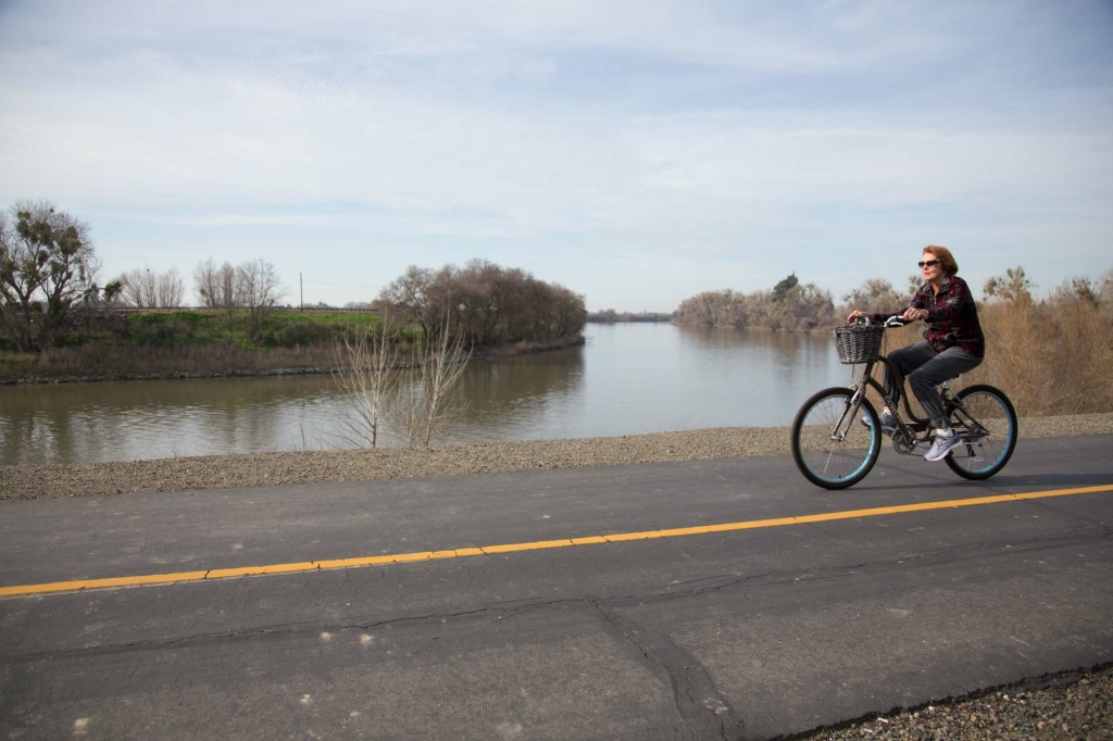 A bicyclist rides along a public levee in the Pocket in the Meadowview neighborhood of Sacramento on Thursday, Feb. 11, 2016. Darryl Lucien, who works for a state assemblyman, says this undeveloped, city-owned field is often
