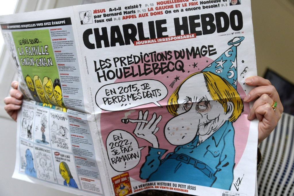 A person reads the latest issue of the French satirical newspaper Charlie Hebdo in Paris on Jan. 7, 2015, after gunmen armed with Kalashnikovs and a rocket-launcher opened fire in the offices of the weekly in Paris, killing at least 11.