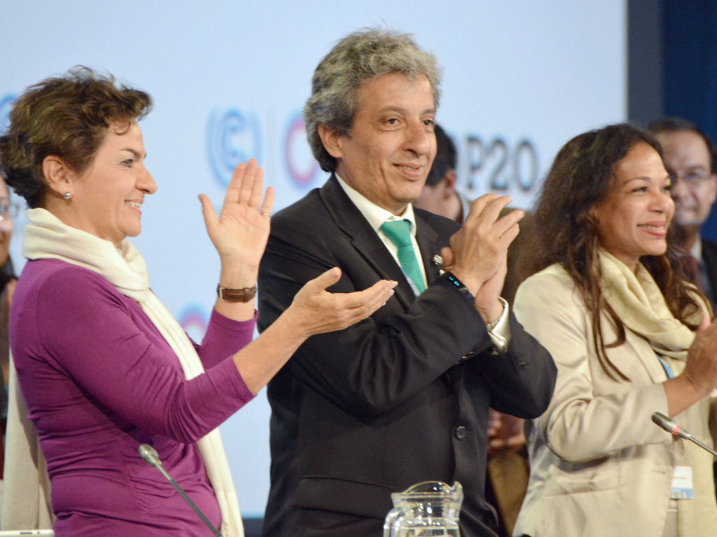Manuel Pulgar-Vidal (center), Peru's environment minister applauds after delegates to the Lima climate conference agreed on a deal to cut greenhouse gas emissions on Saturday.
