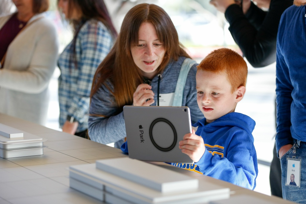 Logan Roe, 7, tries out the augmented reality system that shows what the finished Apple Park will look like at the opening of the Apple Park Visitor Center on November 17, 2017 in Cupertino, California.