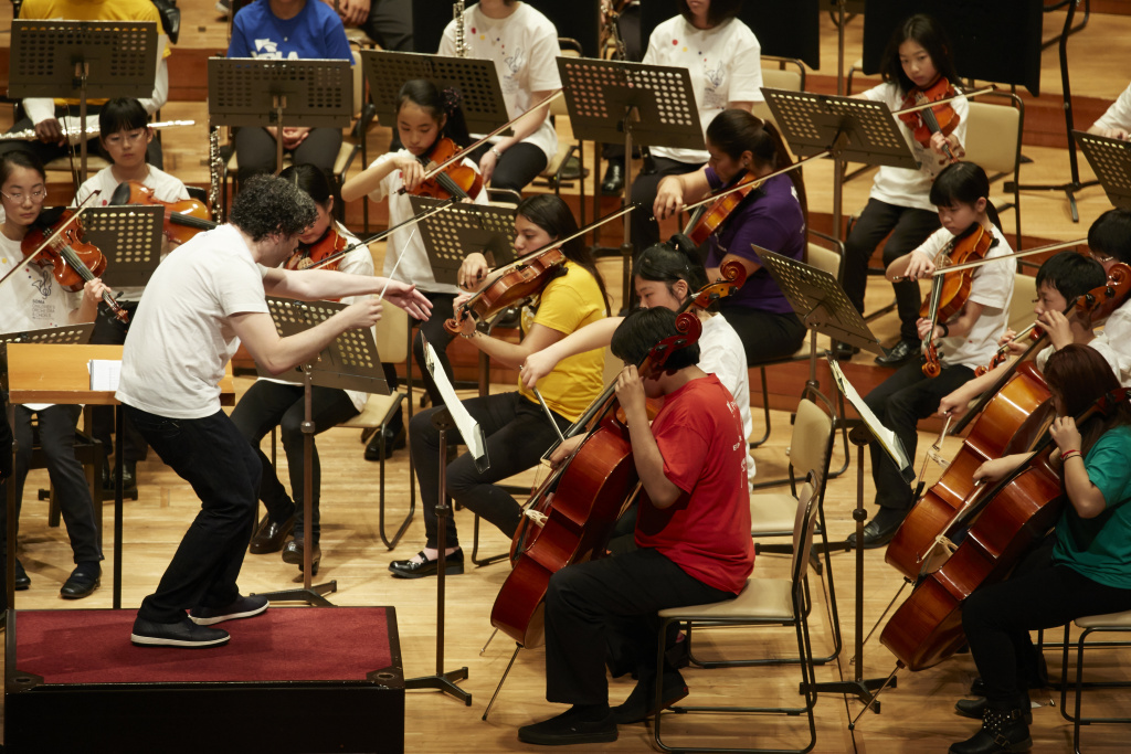 LA Philharmonic's music and artistic director Gustavo Dudamel conducts a rehearsal at Tokyo's Suntory Hall with an orchestra comprised of children from Youth Orchestra L.A. (YOLA) and from the El Sistema orchestra in Soma, Japan. Members of YOLA will be performing at the Super Bowl 50 halftime show on Sunday, Feb. 7.