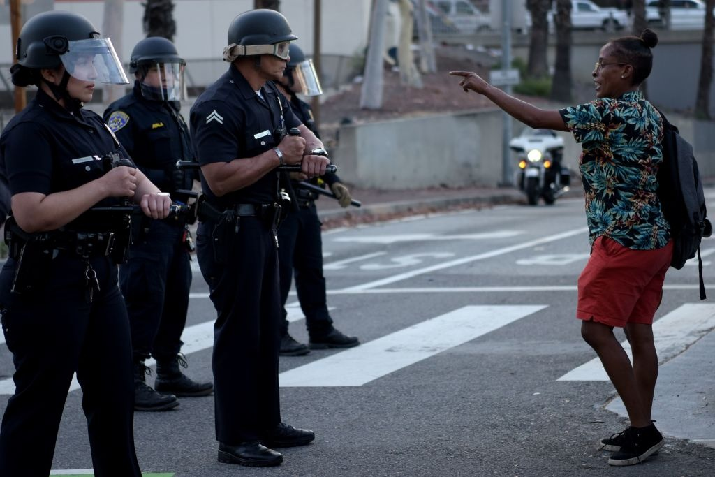 A woman gestures to a row of police officers as protesters gather in downtown Los Angeles on May 27, 2020 to demonstrate after George Floyd, an unarmed black man, died while being arrested by a police officer in Minneapolis who pinned him to the ground with his knee.