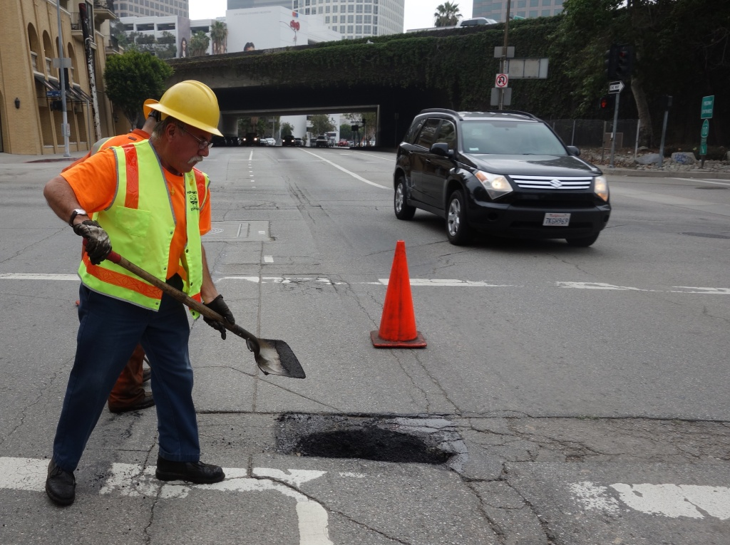 FILE PHOTO: Los Angeles city worker Hugo Vasquez shovels asphalt into a pothole in May 2015.