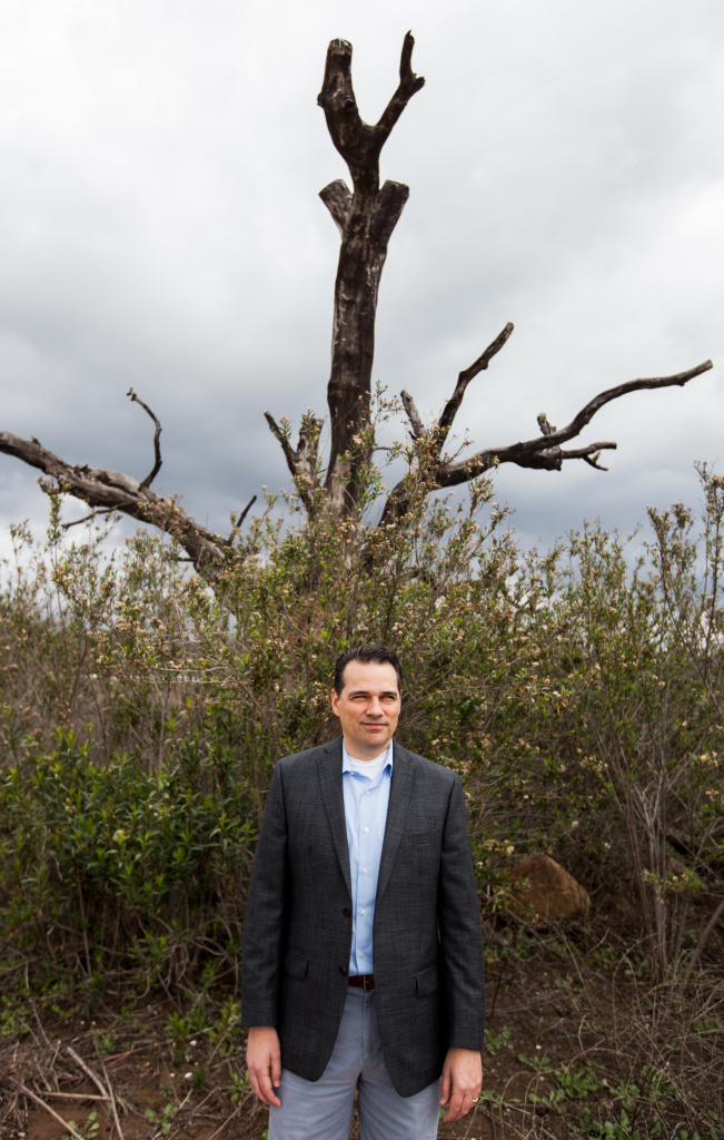 Ron Merckling, public affairs and water resources manager at the Casitas Municipal Water District, stands in front of a dead tree that used to be submerged by waters of Lake Casitas.