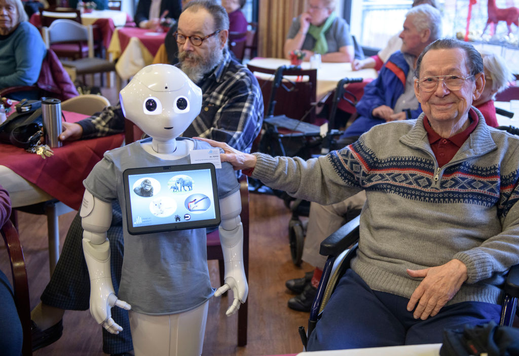 An elderly resident is being cared for by a robot.