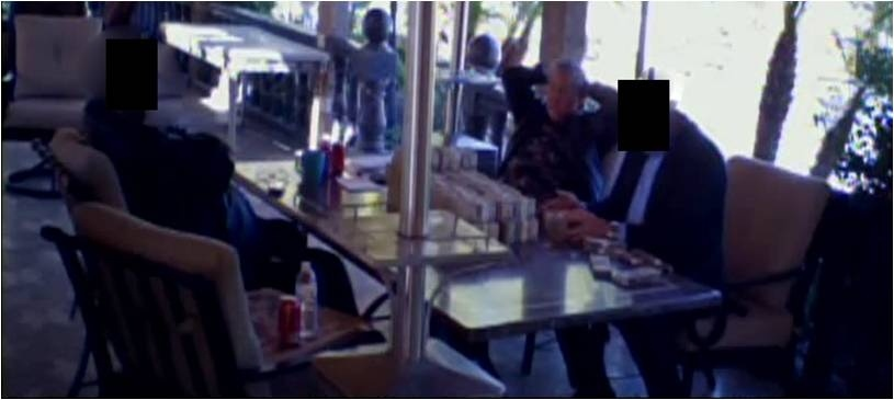 The U.S. Attorney's Office says this is a capture from a video in which Marcelo Co – an ex-Moreno Valley city councilman – accepts a $2.36 million bribe on January 30, 2013. Co is with his hands on the back of his head, sitting in front of the cash, the feds said. The other two people in the photo are an undercover law enforcement agent and an informant, both of which officials declined to identify.