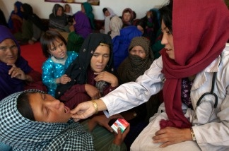 Mid-wife Raqaiu Khoshnod examines a woman at a mobile health clinic June 9, 2011, in the mountain village of Raquol, in Panjab district, Afghanistan.