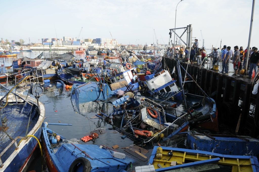 Fishing boats washed ashore by a small tsunami, sit in Caleta Riquelme, adjacent to the port, in the northern town of Iquique, Chile, after magnitude 8.2 earthqauke struck the northen coast of Chile, Wednesday, April 2, 2014. Authorities lifted tsunami warnings for Chile's long coastline early Wednesday. Six people were crushed to death or suffered fatal heart attacks, a remarkably low toll for such a powerful shift in the Earth's crust.