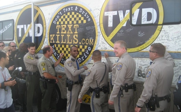 CHP and local police officers at Dodger Stadium Oct. 14, 2010, sign the exterior of a trailer that encourages people to pledge not to text while driving.