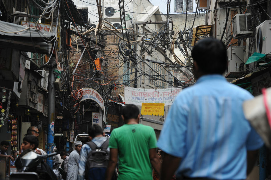 Indian pedestrians walk on a street under electric wires in the old quarters New Delhi on July 31,2012. A massive power failure hit India for the second day running as three regional power grids collapsed, blacking out more than half the country in a crisis affecting over 600 million people.