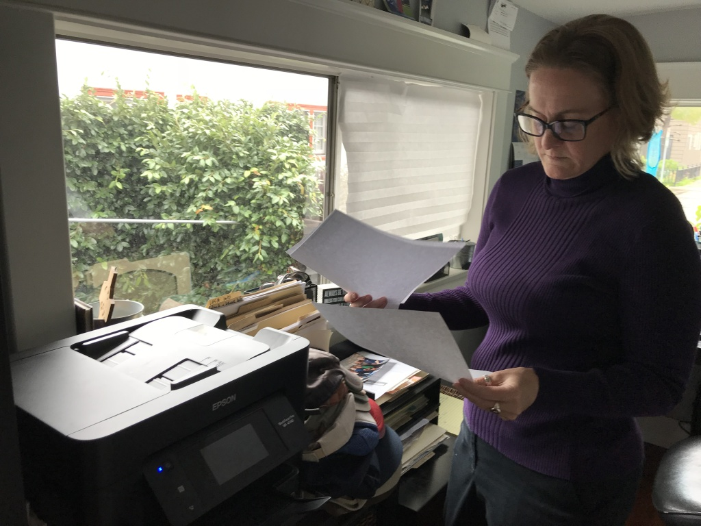 Heather Altman looks through old health insurance bills in her Long Beach home office, Jan. 16, 2019 (David Wagner/KPCC)